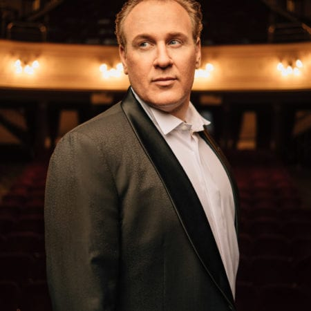 Lucas Meachem, Baritone, dramatically-lit and wearing a tuxedo in an empty theatre, looking off to the left.